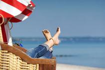 Dame mit nackten Füßen im Strandkorb