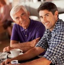 Zwei Männer trinken einen Kaffee und einen Espresso, ein Glas Wasser steht dabei, älterer und jüngerer Mann