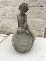 Junge auf Kugel sitzend