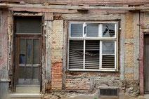 Marode Gebäudefront mit Tür und Fenster