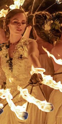 Die Entspannungsfee spielt mit brennenden Fächern bei einer Feuershow