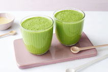 Zwei Trinkgläser gefüllt mit grünem Spinat-Smoothie, angerichtet auf einem altroséfarbenen Keramikbrettchen.
