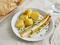 Spargel mit Salzkartoffeln, angerichtet auf einem weißen Teller, garniert mit frischer Petersilie.