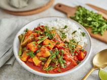 Thai-Curry serviert auf einem hellen Teller.
