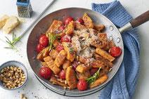 Süßkartoffel-Gnocchi mit Kirschtomaten, Pinienkernen und Parmesan, angerichtet in einer Pfanne neben einem blauen Geschirrtuch auf weißem Hintergrund.
