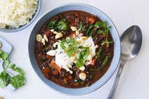 Belugalinsen-Curry, serviert in einer hellblauen Keramikschüssel.