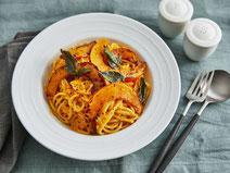 Spaghetti mit Kürbissauce angerichtet auf einem weißen Teller.
