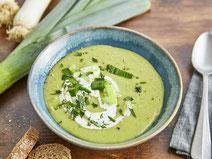 Vegane Kartoffel-Lauch-Suppe serviert auf einem türkisfarbenen Suppenteller.