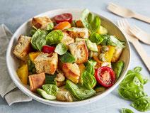 Zuckerschoten-Salat serviert in einer Salatschüssel, dazu geröstetes Brot.
