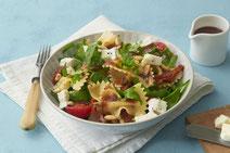 Nudelsalat mit Rucola serviert auf einem weißen Teller.