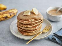 Vegane Bananen-Haferflocken-Pancakes serviert auf einem Dessertteller mit goldener Dessertgabel.