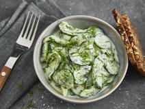 Gurkensalat mit saurer Sahne angerichtet in einer hellgrauen Salatschüssel, serviert mit zwei Scheiben Vollkornbrot.