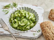 Gurkensalat mit Essig-Öl-Dressing serviert in einer weißen Salatschüssel auf einem weißen Holzbrett.