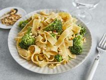Bandnudeln mit Brokkoli und Pinienkernen, angerichtetn auf einem weißen Teller, serviert auf einem Esstisch mit weißer Tischdecke.