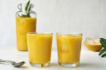 Mango-Smoothie, serviert in zwei gläsernen Trinkgläsern.