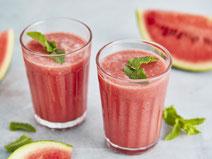 Melonen-Smoothie, serviert in zwei gläsernen Trinkgläsern.