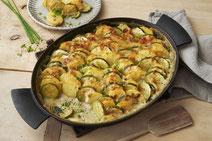 Kartoffel-Zucchini-Auflauf serviert in einer schwarzen Auflaufform.