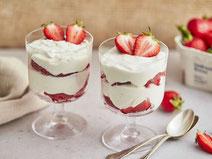 Erdbeer-Quark serviert in zwei Gläsern, garniert mit ein paar Scheiben frischer Erdbeeren.