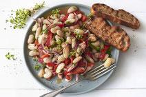 Mediterraner Weiße-Bohnen-Salat und geröstetes Brot angerichtet auf einem hellgrauen Teller mit silberner Gabel, serviert auf einem weißen Holzhintergrund.