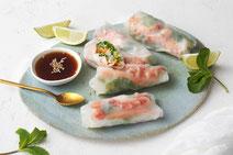 Vietnamesische Sommerrollen angerichtet auf einer hellblauen Tontafel, serviert mit Sojasauce in einem kleinen, weißen Schälchen und drei Viertelstücken Limetten.