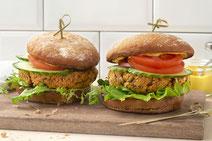 Zwei Kichererbsen-Burger auf einem Schneidebrett aus Holz.