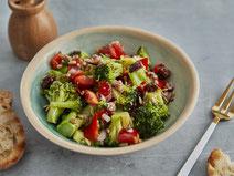 Brokkoli-Salat angerichtet auf einem hellblauben Teller.