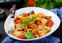 Mediterran zubereitetes Hühnchen mit Aubergine und Pasta.