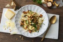 Pilzrisotto serviert auf einem weißen Teller.