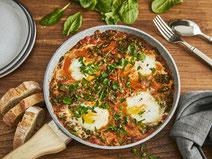 Spinat-Shakshuka angerichtet in einer Pfanne, serviert auf einem dunklen Holztisch, mit Baguette gereicht.