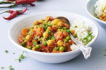 Indisches Curry, serviert in einer weißen Porzellanschüssel.