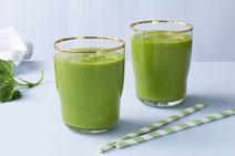 Zwei Trinkgläser mit Goldrand gefüllt mit grünem Mangold-Smoothie, daneben zwei grün-weiße Papiertrinkhalme.