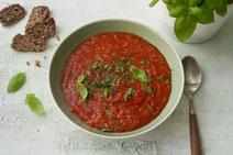 Tomatensuppe mit Reis serviert in einem hellen Suppenteller.