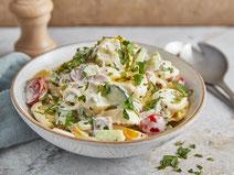 Tortellinisalat serviert in einer weißen Salatschüssel.