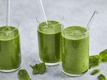 Grüner Smoothie in drei Trinkgläsern, serviert mit einem durchsichtigen Strohhalm.