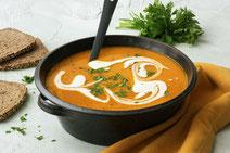 Kürbissuppe serviert in einem schwarzen Kochtopf.