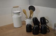 Kaffeetassen und Michkannen in einer Ausstellungsküche