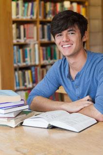 junger mann mit buch in bibliothek