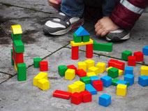 Kind spielt mit bunten, unterschiedlich förmigen Holzklötzen