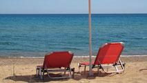 Zwei rote, leere Liegestühle und ein roter Sonnenschirm am menschenleeren Zaga-Strand. Individuelle Angebote: Ihre Wünsche und Ideen im Rahmen meiner Möglichkeiten.