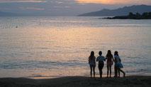 10-jährige Kinder spielen am Strand bei Sonnenuntergang. Kinderbetreuung