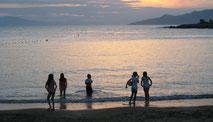 Fünf Kinder spielen am Ufer des Meeres.
