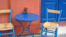 Zwei typisch griechische blaue Stühle an blauem rundem Tischchen.