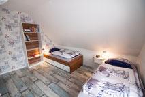 Schlafzimmer mit Einzelbetten und maritimer Tapete