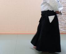 画像③魂氣が側頸に結ぶと同時に同側の足先を後方に置き換えて軸とし(袴の下に見えるのは左足で、置き換えて軸とした右足は見えない)、