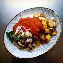 Schnitzel mit Bratkartoffeln und Champignonrahmsoße auf ovalem Teller