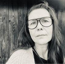 Frau mit Brille an Holzwand gelehnt