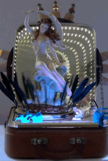 Assemblage light sculpture made from a 1950's portable record player, an infinity mirror, radio tubes, feathers, plastic animal toys, and a sensuous woman sitting on top of the platter who revolves in space as the platter turns.