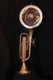 "Assemblage light art sculpture made from a silver baritone horn, a chrome reflector dish, and a collection of painted watch springs which ""shimmy"" as they revolve around an axis."
