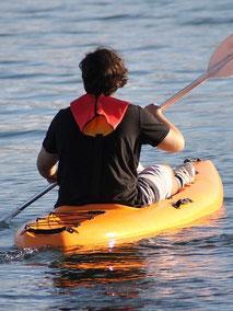 Mann paddelt allein im Einer-Paddelboot Kajak über einen See in Meck-Pomm