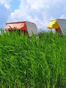 Ruhe im Deutschland-Urlaub: zwei Strandkörbe an der Ostsee mit gelber und roter Markise